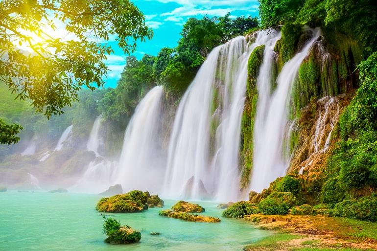 Photo of waterfall and greenery with sun