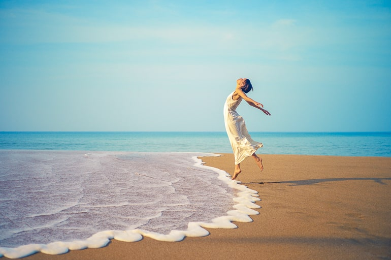 Woman jumping on beach with water and sand underneath her