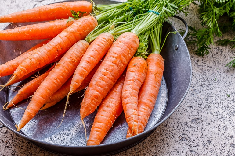 orange carrots with stems on metal plate