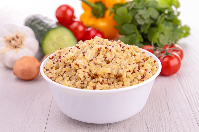 white bowl of quinoa with vegetables behind top alkaline foods