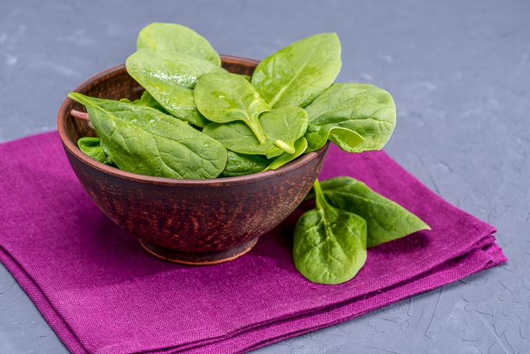 green spinach leaves in brown bowl on purple napkin