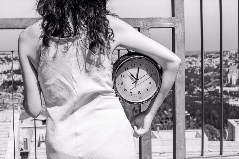 black and white photo of woman holding clock under arm what not to do on a first date