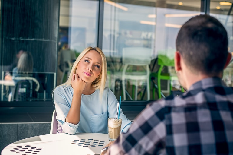 woman looking bored at table while man talks what not to do on a first date