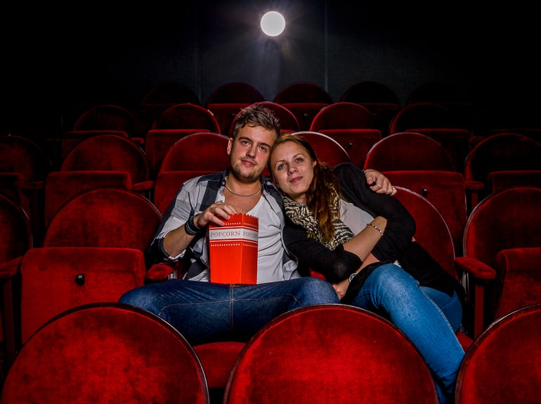 man and woman sitting in movie theatre on red chairs
