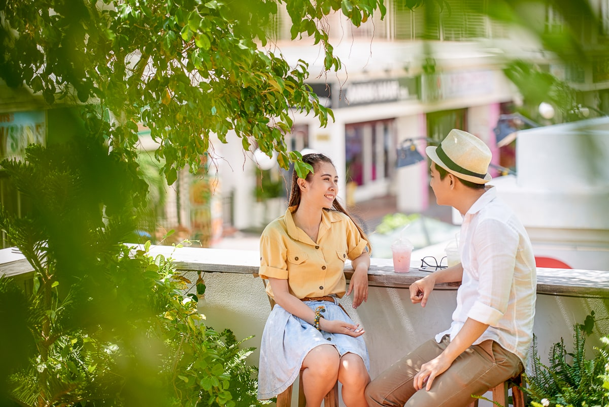 Couple sitting on stools talking to each other with greenery around what to talk about on a first date