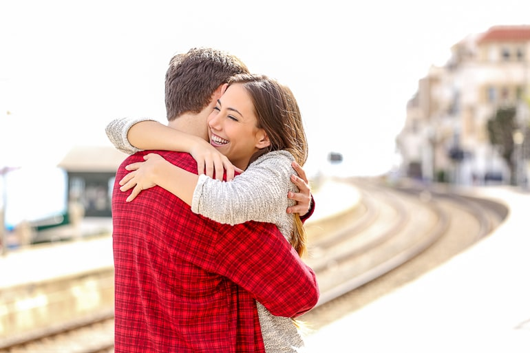 man in red shirt hugging smiling woman with blurry background