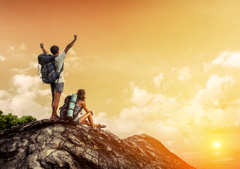Man and woman hiking on rock with yellow sky and sunset in background