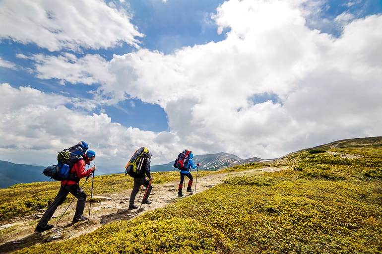 Three people with backpacks and hiking poles walking up a hill
