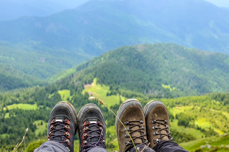 Hiking boots with trees and mountains in background