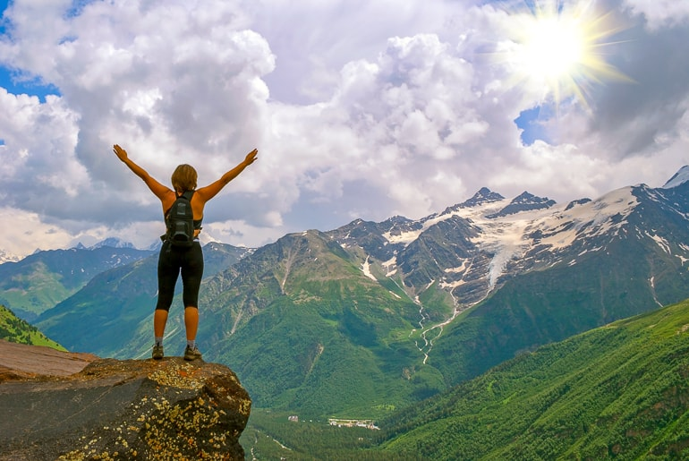 Woman Hiker standing on rock raising her arms with sun and mountains in background