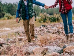 Man and woman with hiking boots and vests walking over rocks on ground benefits of hiking