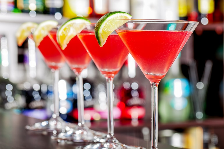 red cosmo drinks in tall wide brimmed glasses on bar top
