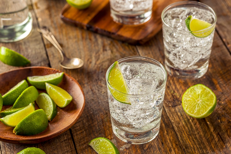 two gin and tonic cocktails in wooden top with limes around