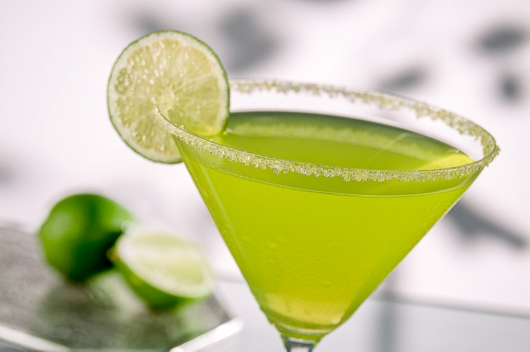 margarita in wide brimmed glass with salt and circle of lime