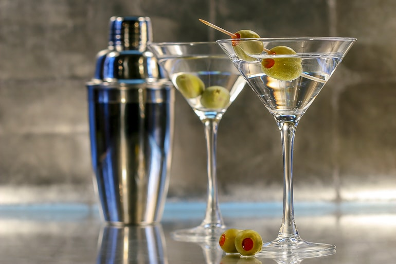 two martinis with olives and a silver shaker behind