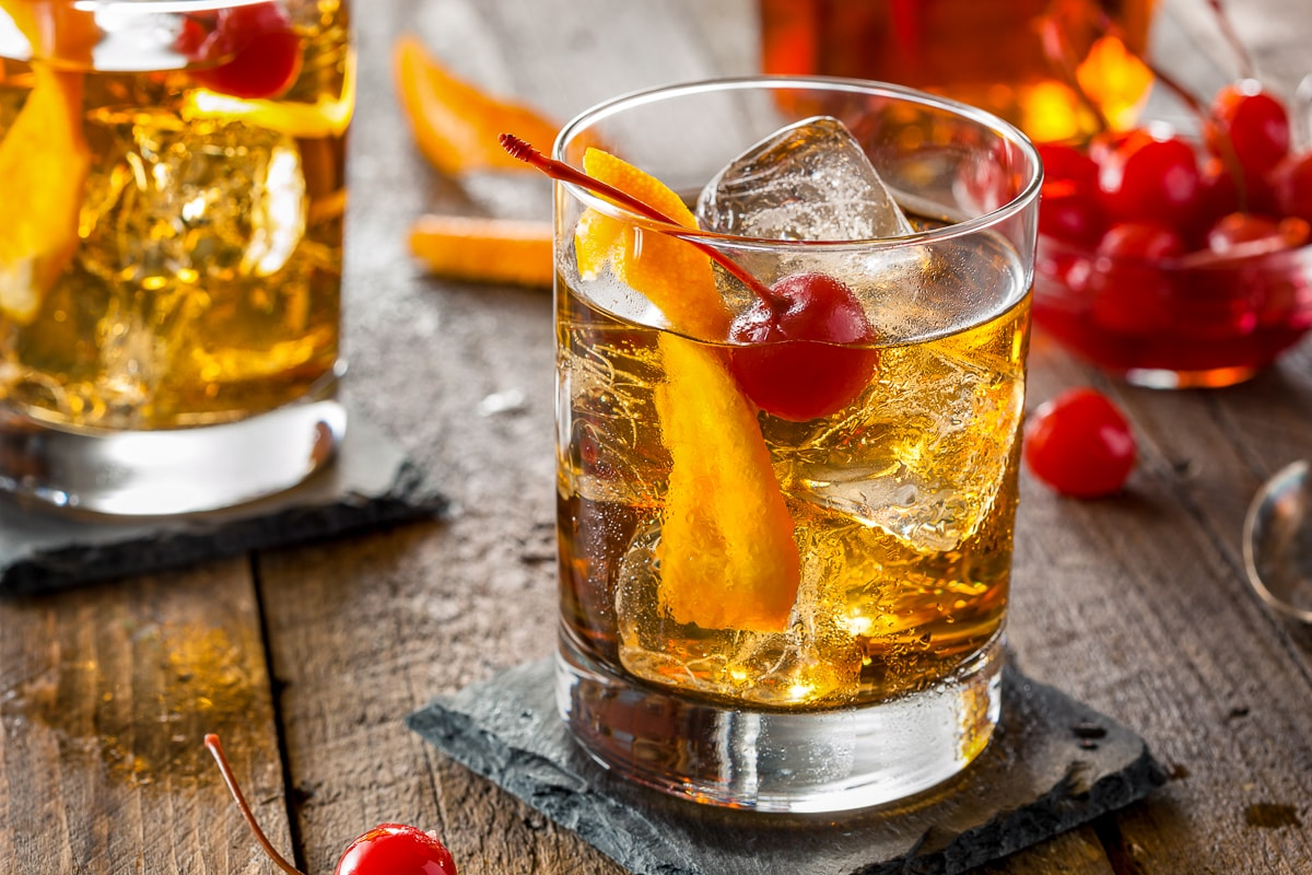 orange drink with ice and cherry in short glass best alcoholic drinks