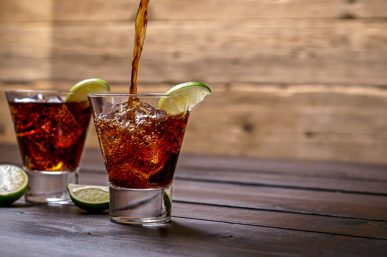 two short glasses with rum and coke with slices of limes