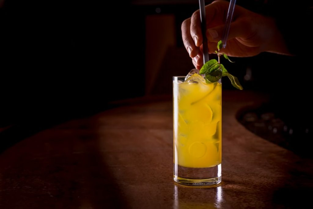 tall glass with vodka and orange juice on wooden table best alcoholic drinks
