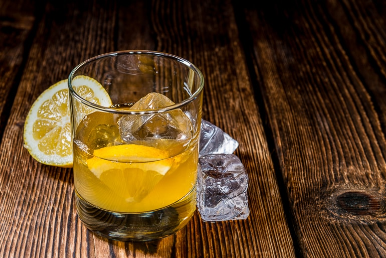 cloudy drink with ice and orange in short glass in wooden table whiskey sour