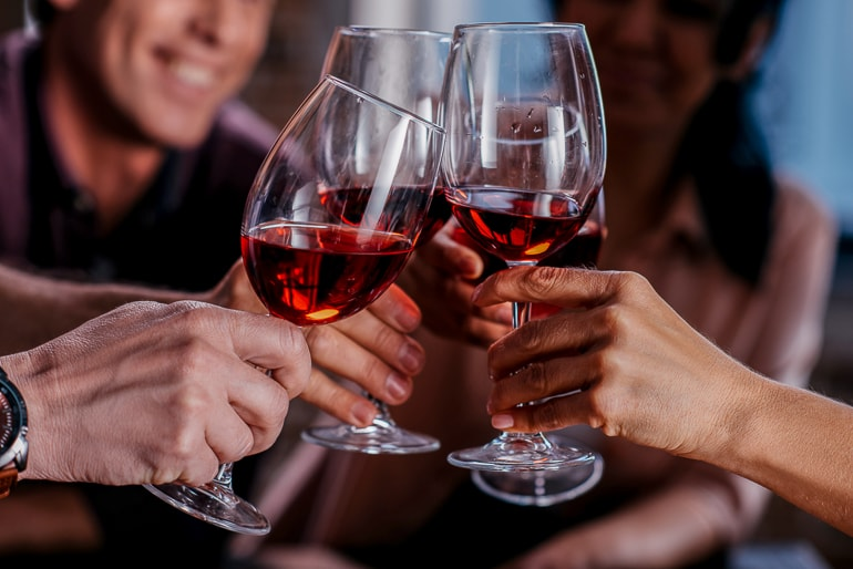 glasses of red wine in hands clinking together