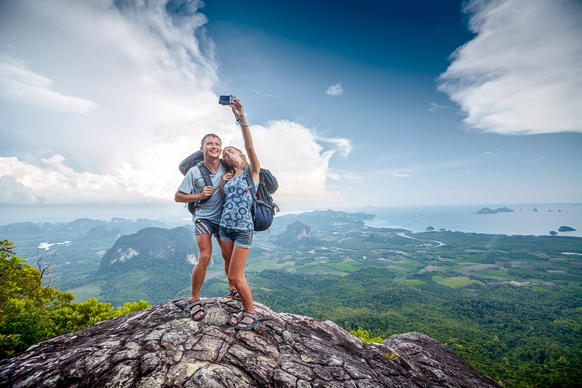 Couple with backpacks taking photo of themselves on rock captions for pictures of yourself