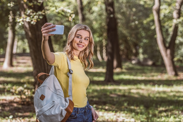 Woman in yellow top with backpack taking photo of herself