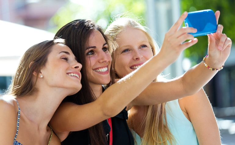 Group of young women taking selfie with blue phone