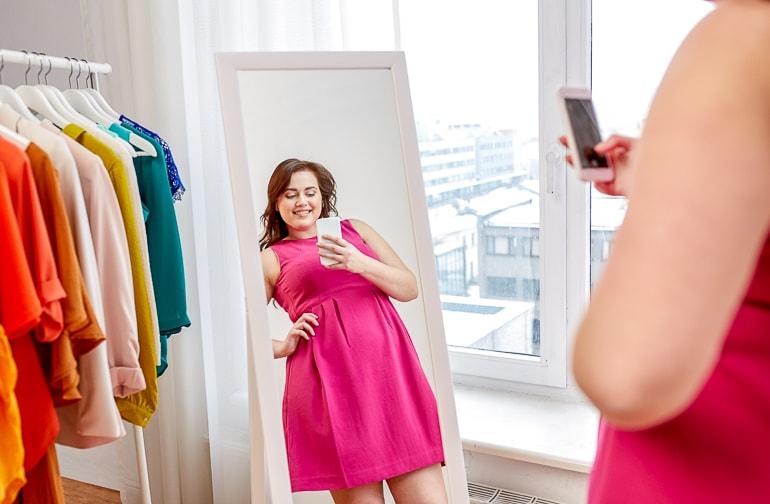 Woman in pink dress taking selfie in mirror