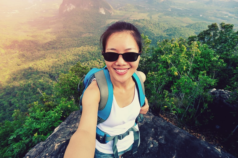 Woman with sunglasses and backpack taking photo of herself on rock