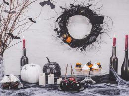 fake spider webs and wine bottles on table cheap halloween decorations