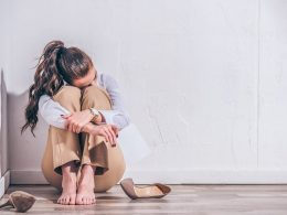 Woman sitting on floor hugging her legs with shoes next to her coping strategies for anxiety