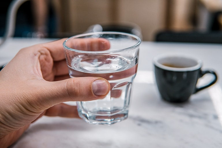 Hand holding glass on water with dark mug in background