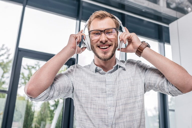 Man with glasses wearing white headphones and laughing