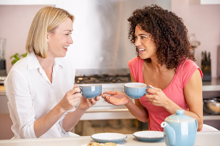Two woman talking to each other while holding blue mugs