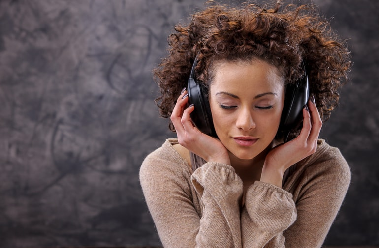 Woman having eyes closed while wearing dark headphones