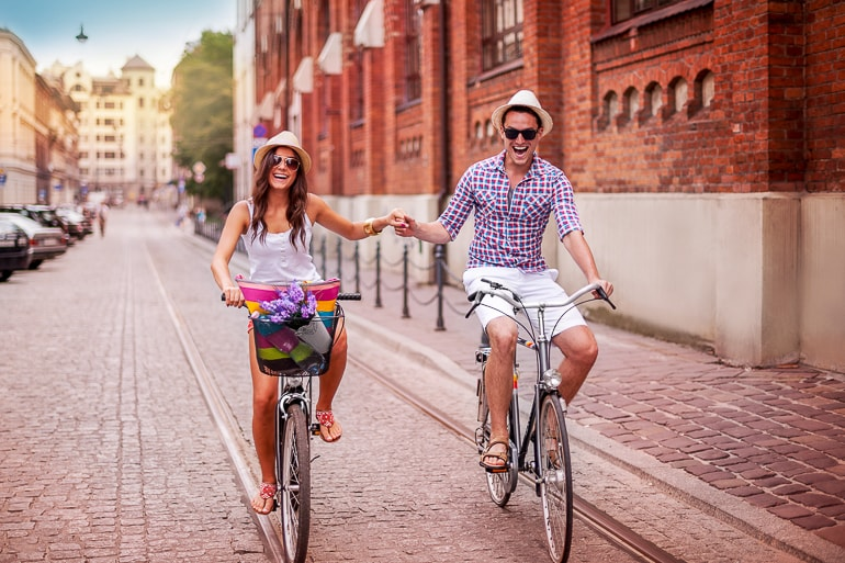 Man and woman riding bikes while holding hands and laughing funny captions