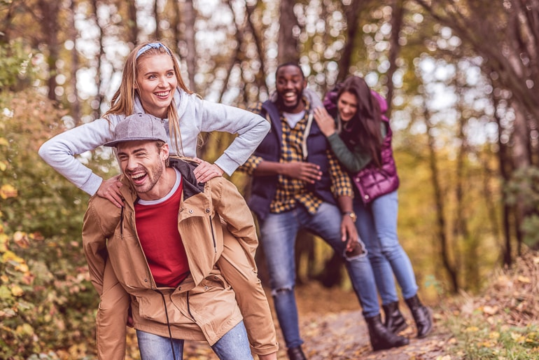 Four friends in forest playing and laughing