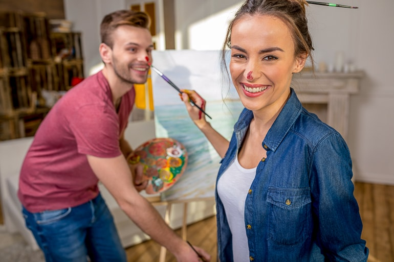 Man and woman holding paint brushes and having paint on their nose