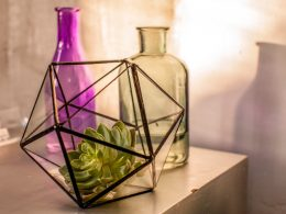 black metal terrarium on table with light behind geometric decor pieces