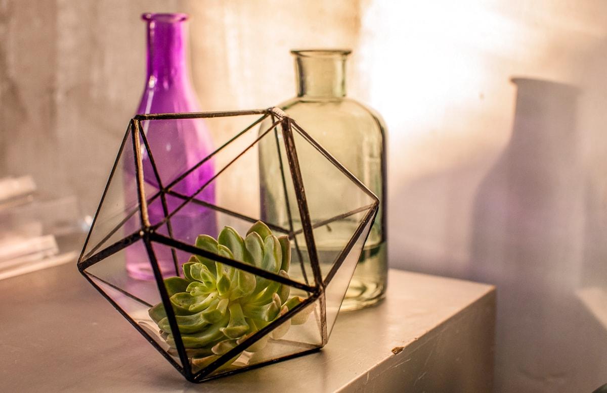 black metal terrarium on table with light behind geometric decor pieces