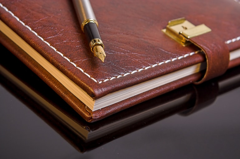Brown leather bound journal with fountain pen on top