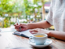 Woman writing in journal with mug of tea on table next to her how to keep a journal