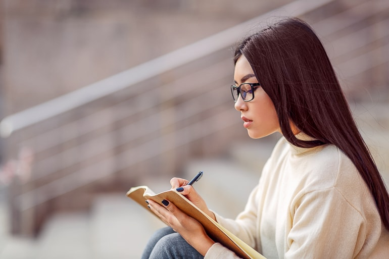 Woman with glasses holding journal with hands and writing