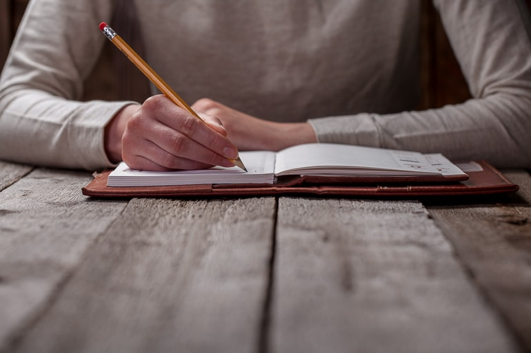 person holding pencil and writing in journal on table in front of them