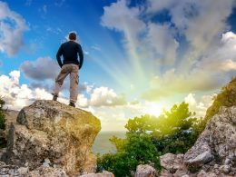 Man standing on rock looking at water blue sky and sun instagram captions for boys