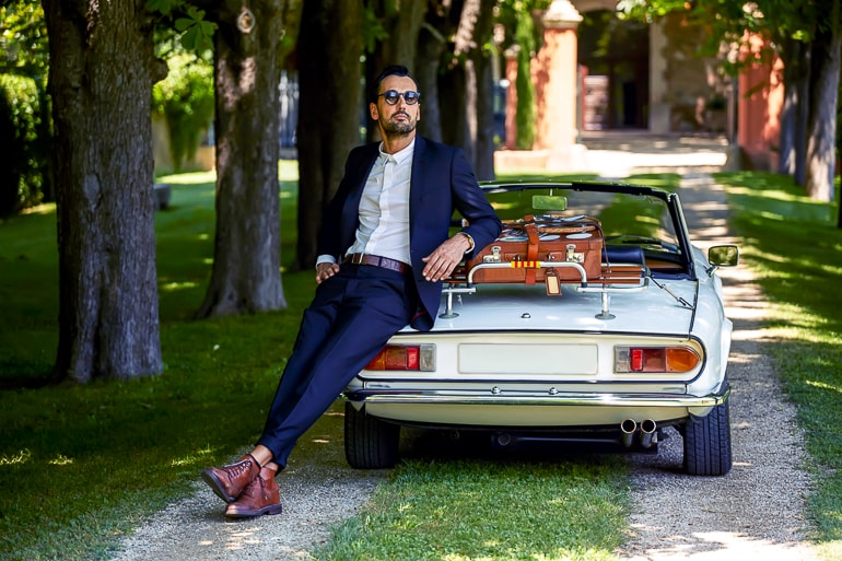 Man in suit leaning against vintage car with trees in background instagram captions men