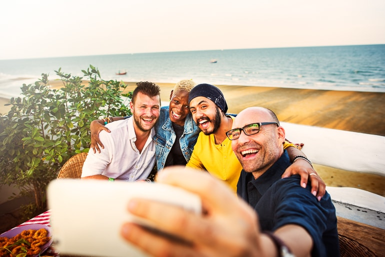 group of men taking selfie with beach and ocean in background