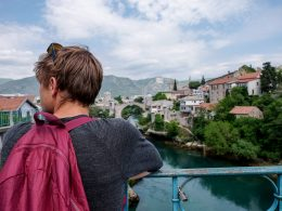 boy looking over water with backpack on no poo experience