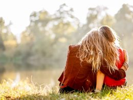 Backs of two girls sitting on grass and hugging each other picture captions for girls