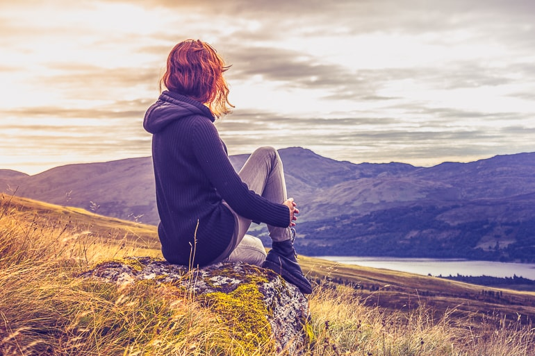 Woman sitting on rock looking out at hilly landscape in background